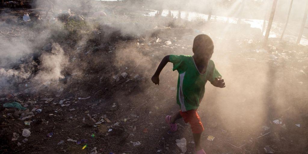 Un niño iluminado por un rayo de sol atraviesa corriendo una nube de humo cerca del río Níger, en Bamako, Mali.